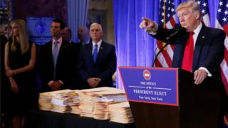 Donald Trump points at the press while standing next to a table covered in documents at a news conference