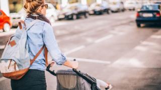 Parent pushing a pram along a road
