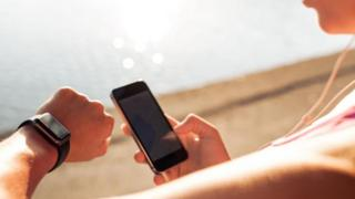Una mujer chequeando su reloj inteligente y su teléfono celular