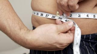 Hombre midiéndose la cintura