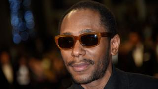 "This file photo taken on May 17, 2015 shows US rapper Yasiin Bey formerly Mos Def posing as he arrives for the screening of the film ""Amy"" at the 68th Cannes Film Festival in Cannes, southeastern France"