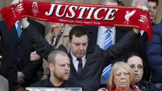A Hillsborough family campaigner holding up a justice scarf