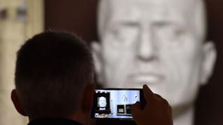 A man takes a picture of the tomb of Italian dictator Benito Mussolini