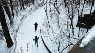 Two people ski in a park