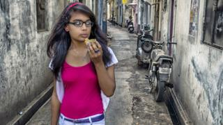 Young women eating a samosa