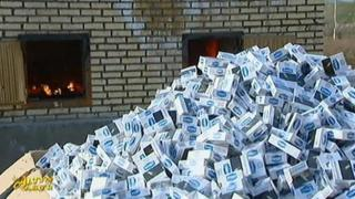 A pile of cigarette packs next of a fiery furnace