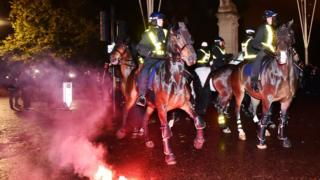 A red flare in front of police horses