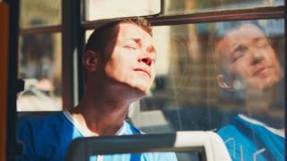 Un hombre dormido en el un autobús