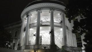 The White House at night decorated with fake cobwebs and spiders.