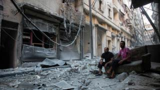Syrians sit and look at the rubble following an airstrike on the regime-controlled neighbourhood of Karm al-Jabal on September 18, 2016.