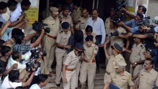 Indian police are surrounded by media as they escort former media executive Indrani Mukherjea (C) from a city court in Mumbai on August 31, 2015