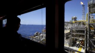 Oct. 28, 2010 file photo, an oil worker looks at a Petrobras offshore ship platform over Tupi field in Santos Bay off the coast of Rio de Janeiro, Brazil
