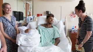Un paciente joven en camilla sonríe a dos muchachas de pie