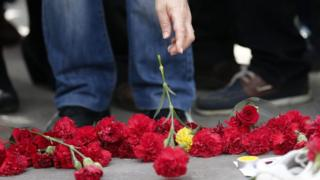 People place flowers on the ground second day after the explosions after the anti-government protest in Ankara Turkey