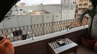 """A picture taken from street artist Banksy""""s newly opened Walled Off hotel in the Israeli occupied West Bank town of Bethlehem, on March 3, 2017, shows Israel""""s controversial separation wall."""