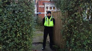 Policeman standing in front of a house