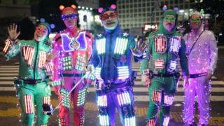 People dressed in bright neon suits covered in lights.