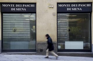 A man walks in front of the Monte dei Paschi bank in Siena, Italy.