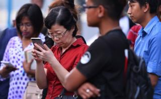 China's consul-general checks her phone at a jetty in Kota Kinabalu after a tourist boat carrying 28 Chinese nationals was reported missing on January 28.