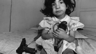 Una niña de tres años sostiene una paloma llamada Esperanza y al lado tiene un arma en Watts, Los Ángeles.