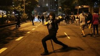 A demonstrator throws stones at riot police during a protest against Brazil's new President Michel Temer after the Senate removed former President Dilma Rousseff in Sao Paulo, (02 September 2016)