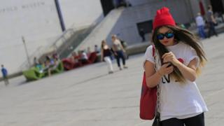 A woman in Vienna walking along while looking at a mobile phone