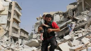 A Syrian man carries a baby after removing him from the rubble of a destroyed building following a reported air strike in the Qatarji neighbourhood of the northern city of Aleppo on 21 September