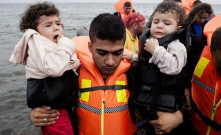 A refugee man carries children upon their arrival on Sykamia beach, west of the port of Mytilene, on the Greek island of Lesbos after crossing the Aegean sea from Turkey on September 22, 2015.