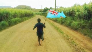 A Fiji boy runs down a dirt road, cheering on the rugby sevens team