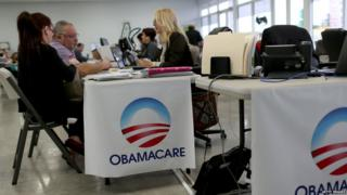 Aymara Marchante (L) and Wiktor Garcia sit with Maria Elena Santa Coloma, an insurance advisor with UniVista Insurance company, as they sign up for the Affordable Care Act, also known as Obamacare, before the February 15th deadline on February 5, 2015 in Miami, Florida