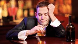 Un hombre tomando con desánimo en un bar.