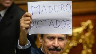 جلسه ویژه پارلمان در روز یکشنبه در کاراکاس پرهرج و مرج بود. یک نماینده مخالف شعار ضدمادورو نمایش می دهد