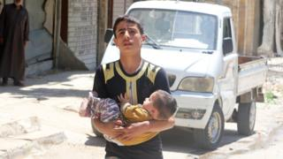 A boy carries a baby to safety in the rebel-held al-Fardous area of Aleppo, Syria, 29 April