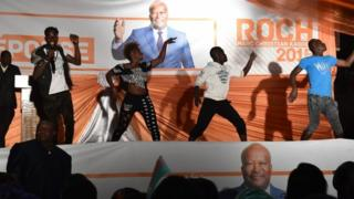 Artists perform before a banner of Burkina Faso's new president Roch Marc Christian Kabore in Ouagadougou on 1 December 2015