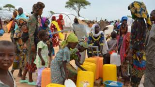 Displaced Nigerians who have fled Boko Haram fill water containers at a camp in Niger