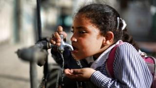 Girl drinking from outside tap