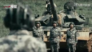 Three men in uniform standing in front of a tank, with the back of the head and shoulders of the man giving them orders in the foreground