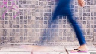 Blurry woman walking past wall