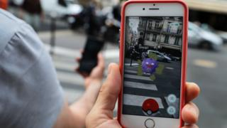 "This picture taken on July 26, 2016 near the Louvre museum's pyramide in Paris shows the ""Pokemon Go"" app on the screen of a smartphone"