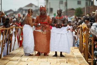 Newly crowned Oba of Benin Eheneden Erediauwa is guided through a symbolic bridge b palace chiefs during his coronation in Benin City, Nigeria