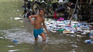 Niño en un camino inundado en Santo Domingo