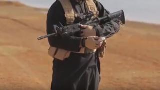 Screenshot from the execution video showing an IS solider armed with a rifle and radio transmitter