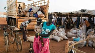 An asylum seeker and her baby from Sudan, who recently arrived in South Sudan, stands beside a truck holding some of her belongings before she is transferred to the refugee camp in Ajuong Thok, near Yida, northern South Sudan