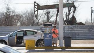 Women pumping gas with oil rig in background