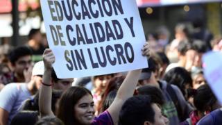 """Una pancarta de una manifestante que dice """"Educación de calidad y sin lucro""""."""