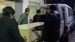 Afghan men unload a coffin of an International Committee of the Red Cross (ICRC) employee, who was killed by gunmen in Jowzjan province, at a hospital in Mazar-e-Sharif (08 February 2017)