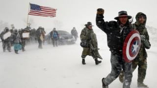 Veterans join activists in a march to Backwater Bridge just outside the Oceti Sakowin camp during a snow fall as water protectors