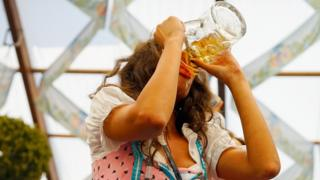 A young woman drinks beer at Hofbraeuhaus beer tent on the opening day of the 2015 Oktoberfest on September 19, 2015 in Munich, Germany