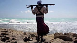 An armed Somali pirate along the coastline (January 2010)
