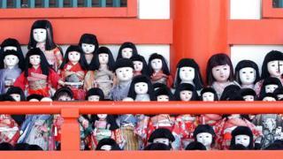 Traditional Japanese dolls lined up at the Awashima Shrine